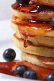 Blueberry pancakes drenched with maple syrup. macro  — Stock Photo