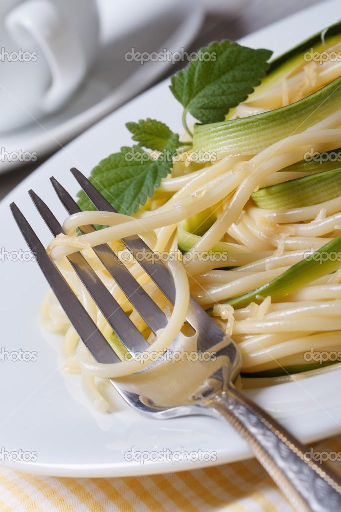 传统的意大利面食意大利面配西葫芦, 奶酪和一把叉子在盘子上表特写 v