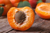 Half ripe apricot closeup on wooden table,  horizontal — Stock Photo