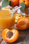 Apricot juice closeup on background basket with fruit.  — Stock Photo