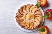 Peach pie and fresh fruit on a wooden top view — Stock Photo