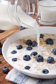 Oatmeal with blueberries and milk is poured from a jug — Stock Photo