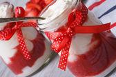 Iogurte de morango em um pote com uma colher horizontal — Fotografia Stock