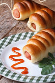 Roll with sausage on a plate with ketchup and arugula vertical — Stock Photo