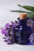 Lavender oil in a blue bottle vertical macro — Stock Photo