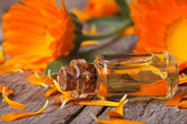 Calendula tincture and flowers on an old table horizontal — Stock Photo