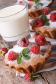 Fresh cupcakes with raspberries closeup and milk vertical — Stock Photo