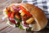 Doner with meat, vegetables and fries in pita bread close-up  — Stockfoto