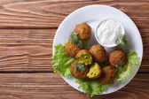 Delicious falafel on lettuce with tzatziki top view — Stock Photo