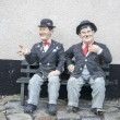 Laurel and hardy sitting on a bench — Stock Photo