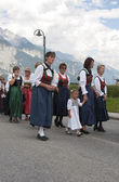 Female and girls walking i traditional dresses in austria proces — Stock Photo