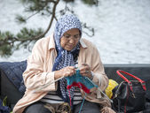Woman knitting on a sofa outsideon multiculture day in holland — Stock Photo