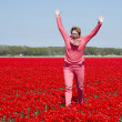 Adult womanjumping  in red tulip field — Foto Stock