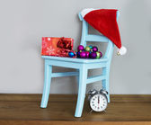 Santa claus hat on chair with presents — Stock Photo