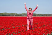 Adult womanjumping in red tulip field — Stock Photo
