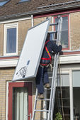 Man climbing the ladder with solar panel — Stock Photo