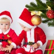 Two children under christmas pine — Stock Photo