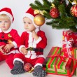 Two children under christmas pine — Stock Photo #15712193