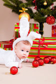 Baby under christmas pine — Stock Photo