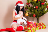Woman with baby near christmas pine — Stock Photo