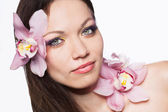 Girl with orchid flowers in hair — Stock Photo
