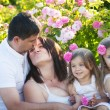 Family in rose garden — Stock Photo