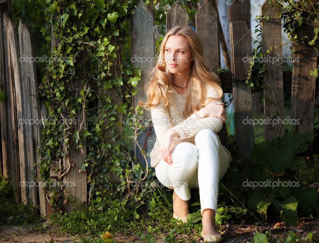 木栅栏附近美丽的金发碧眼女人肖像– 图库图片