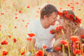 Couple on the poppy meadow — Stock Photo