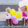 Two little girls with balloons — Stock Photo
