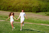 Young couple playing on the meadow — Stock Photo