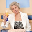 Senior woman with a glass of wine — Stock Photo #37469053