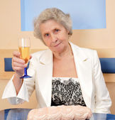 Senior woman with a glass of wine — Stock Photo