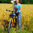 Beautiful smiling girl on bicycle near the golden field — Stock Photo #8883998