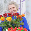 Elderly woman with roses — Stock Photo #8885592