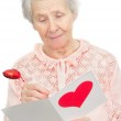 Senior woman hold post-card with heart shape on it cover — Stock Photo #8885941