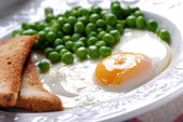 Fried egg served with peas — Photo