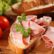 Sliced mortadella on wooden chopping board — Stock Photo