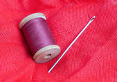 Needle and thread on a red background — Stock Photo