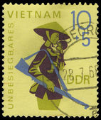 GDR - CIRCA 1968: A stamp printed in GDR, show theVietnam woman with a gun and the child on hands, circa 1968 — Stock Photo