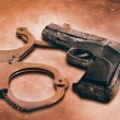 Gun and handcuffs on table. Photo in old color image style — Stock Photo