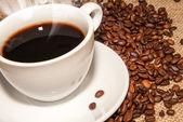 Weiße tasse heißen kaffee und verstreuten kaffee körner — Stockfoto