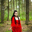 Girl with dreadlocks wrapped in a red knitted scarf in a forest — Stock Photo #16619933