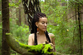 Girl with dreadlocks on the background of birch wood, moss blurr — Stock Photo
