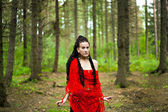 Girl with dreadlocks wrapped in a red knitted scarf in a forest — Stock Photo