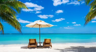 Idyllic white beach in front of the turquoise tropical sea