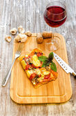 Slice of pizza is on a wooden board — Stock Photo