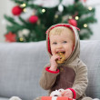 Baby in deer suit with Christmas present box eating cookie — Stock Photo #12444476
