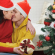Romantic young couple with gift kissing near Christmas tree — Stock Photo