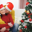 Young man kissing girlfriend near Christmas tree — Stock Photo