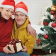 Happy young couple with gift sitting near Christmas tree — Stock Photo